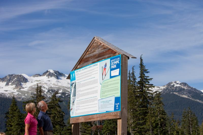 Couple looking at interpretive signage at Whistler Olympic Park